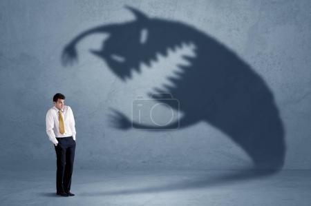 Photo pour Homme d'affaires peur de son propre concept monstre ombre sur fond grungy - image libre de droit
