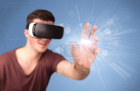 Photo for Young impressed man wearing virtual reality goggles with blue hexagons around him - Royalty Free Image