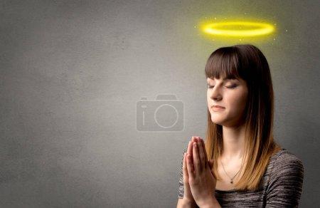 Photo pour Jeune femme priant sur un fond gris avec un halo jaune brillant au-dessus de sa tête - image libre de droit