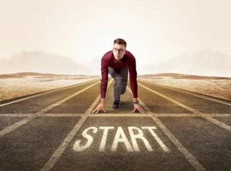 Photo for Young determined businessman kneeling before start line - Royalty Free Image