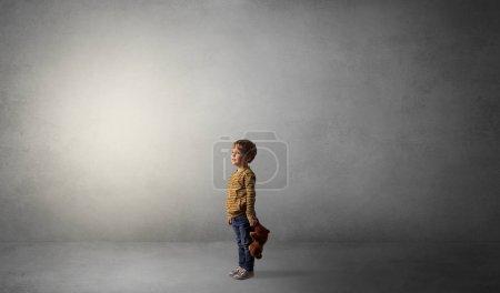 Photo pour Petit enfant waggish rester seul dans une grande pièce vide avec sa peluche - image libre de droit