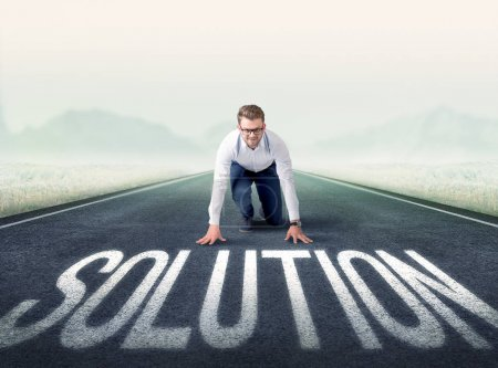 Photo for Young determined businessman kneeling before solution text - Royalty Free Image