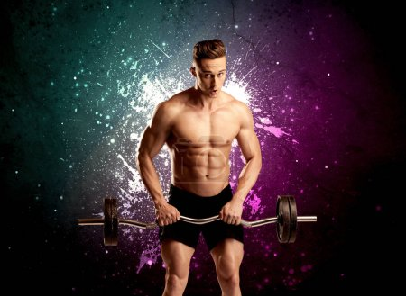 Photo for A sexy male fitness trainer showing his muscles and looking seductive with a weight in his hands in front of bright paint splash purple wall concept. - Royalty Free Image
