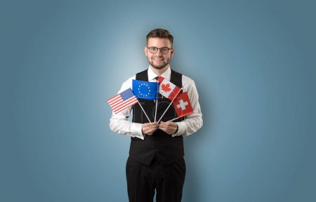 Photo for Cheerful student standing in front of wall with national flag on his hand - Royalty Free Image