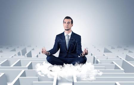 Photo pour Jeune homme d'affaires méditer en position de yoga sur un nuage avec concept de labyrinthe à l'infini - image libre de droit