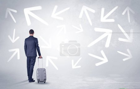 Photo for Businessman with back walking away with higgledy-piggledy arrows around - Royalty Free Image