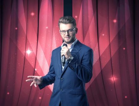 Photo pour Homme d'affaires parlant dans le microphone avec rideau rouge derrière lui - image libre de droit