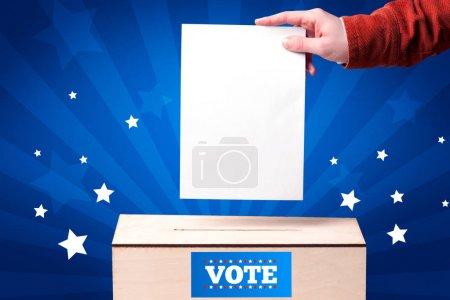 main avec bulletin de vote et boîte en bois