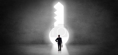 Photo pour Homme d'affaires debout seul devant un gros trou de serrure - image libre de droit
