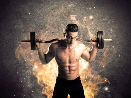 Photo for A strong athletic guy looking seductive while working out with weight in front of a burning fire concrete wall and big flames concept - Royalty Free Image