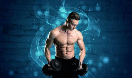 Photo for A sexy body builder lifting weight and showing his muscular, hot body in front of a blue urban brick wall with drawn light beams concept - Royalty Free Image
