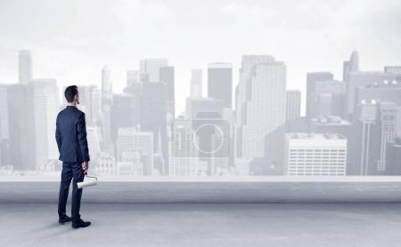 Photo pour Homme d'affaires debout avec le dos sur un toit avec des objets à la main - image libre de droit