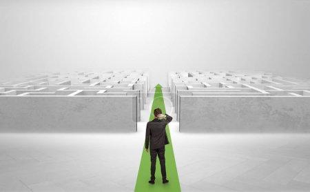 Photo pour Homme d'affaires allant tout droit sur une flèche de tapis rouge entre deux labyrinthe - image libre de droit