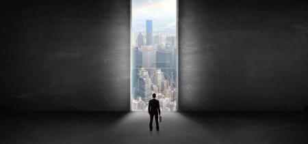 Photo pour Homme d'affaires debout dans une pièce sombre et regardant à l'extérieur d'une vue sur le paysage urbain - image libre de droit