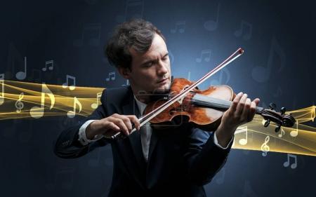 Photo pour Jeune mâle musicien jouant sur son violon avec des notes de musique autour de - image libre de droit