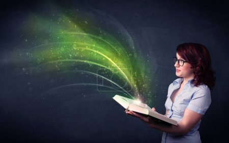 Photo for Casual young woman holding book with green wave flying out of it - Royalty Free Image