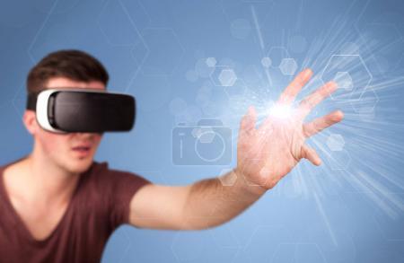 Foto de Joven hombre impresionado con gafas de realidad virtual con hexágonos azules a su alrededor - Imagen libre de derechos