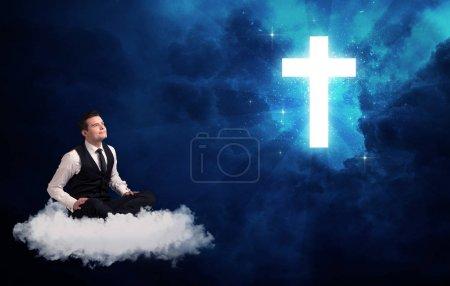 Photo pour Homme d'affaires caucasien assis sur un nuage pelucheux blanc regardant et se demandant à une grande croix brillante - image libre de droit