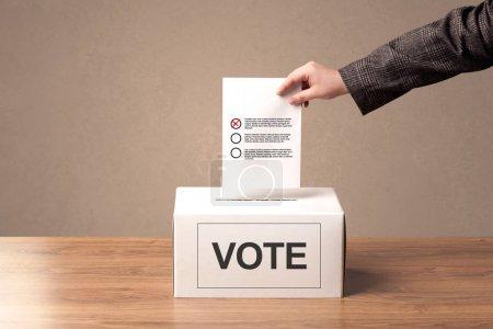 Gros plan de la main masculine qui met le vote dans une urne
