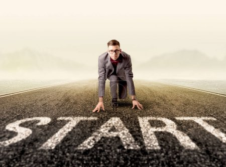 Photo for Young determined businessman kneeling at a start line - Royalty Free Image