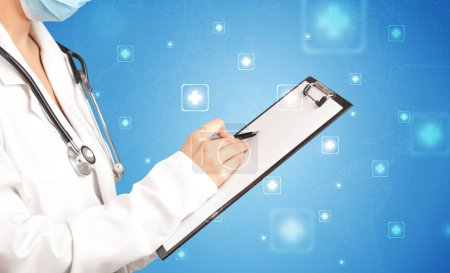 Photo for Female doctor holding notepad with blue background and crosses - Royalty Free Image