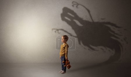 Photo for Scary ghost shadow in a dark empty room with a cute blond child - Royalty Free Image