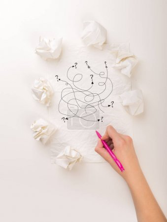 Photo for Female hand next to a few crumpled paper balls drawing random scribbles - Royalty Free Image