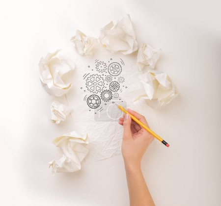 Photo for Female hand next to a few crumpled paper balls drawing rotating gears - Royalty Free Image