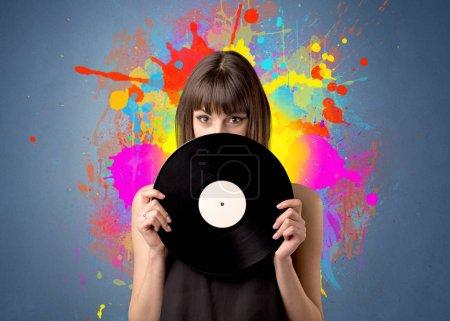 Photo pour Jeune femme tenant un disque de vinyle sur un fond gris avec des éclaboussures colorées derrière elle - image libre de droit