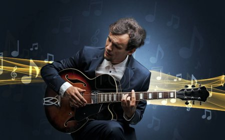 Photo for Young male musician playing on his guitar with musical notes around - Royalty Free Image