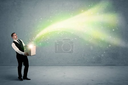 Photo for Bright yellow, green light beams escaping a cardboard box held by young elegant male business person in stylish suit concept. - Royalty Free Image