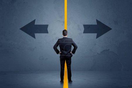 Photo pour Homme d'affaires choisir entre deux options séparées par un concept de flèche de bordure jaune - image libre de droit