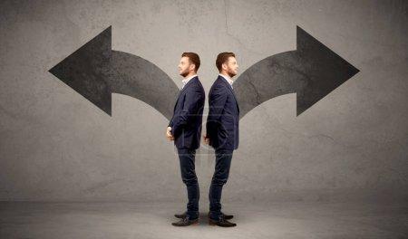 Foto de Jóvenes en conflicto a empresario elegir entre dos direcciones representadas por flechas negras - Imagen libre de derechos