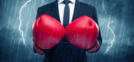 Photo for A dangerous sales person getting ready for a fight concept with red boxing gloves and thunder lightning in background. - Royalty Free Image