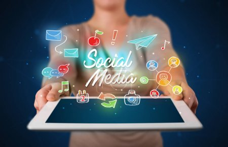 Photo for Casual young woman holding tablet with social media icons - Royalty Free Image
