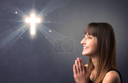 Photo pour Jeune femme priant sur un fond gris avec une croix brillante au-dessus d'elle - image libre de droit