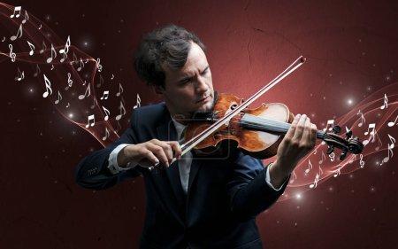 Photo pour Solitaire compositeur musical avec violon et des notes de musique pétillantes autour - image libre de droit