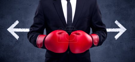 Photo for A confident businessman standing with red boxing gloves on his hand in front of arrows pointing in different directions on urban wall background concept. - Royalty Free Image