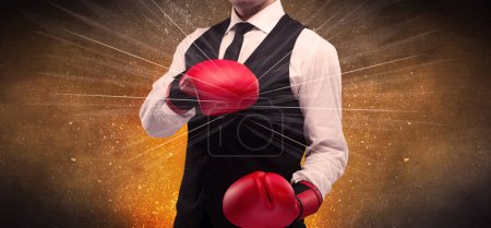 Photo for A successful powerful business person in red boxing gloves concept with illustrated power lines and pieces falling apart in front of explosion. - Royalty Free Image