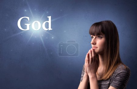 Photo for Young woman praying on a blue background with the word God written above her - Royalty Free Image