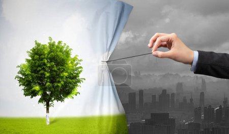 Photo for Hand pulling nature cityscape curtain to gray cityscape, environmental protection concept - Royalty Free Image