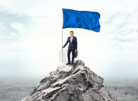 Photo for Handsome businessman on the top of the mountain with blue flag - Royalty Free Image