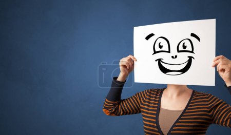 Photo for Casual person holding a paper in front of his face with drawn emoticon face - Royalty Free Image