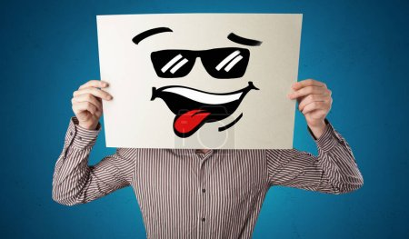 Photo for Casual person holding a paper with cool emoticon in front of his face - Royalty Free Image