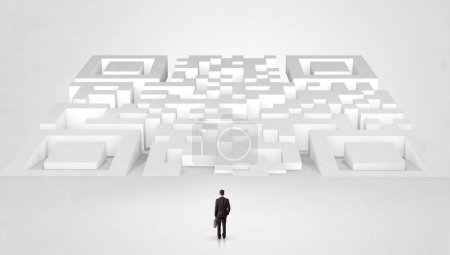 Photo for Businessman standing and thinking in top of a huge maze - Royalty Free Image