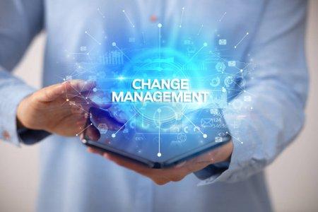 Photo pour Homme d'affaires tenant un smartphone pliable avec inscription CHANGE MANAGEMENT, nouveau concept d'entreprise - image libre de droit