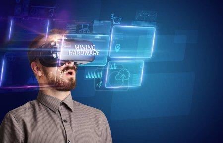 Photo pour Homme d'affaires regardant à travers des lunettes de réalité virtuelle avec inscription MINING HARDWARE, nouveau concept technologique - image libre de droit
