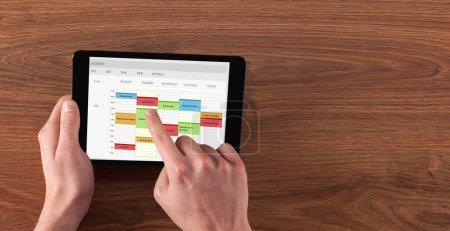 Photo pour Tablette tenue main avec concept horaire et calendrier - image libre de droit