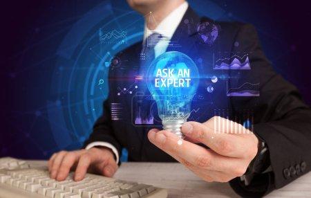 Photo pour Homme d'affaires tenant une ampoule avec inscription ASK AN EXPERT, concept d'idée d'entreprise - image libre de droit