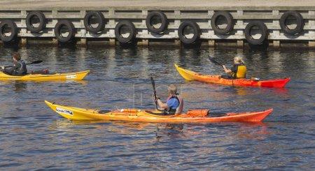 Three kayak rowers